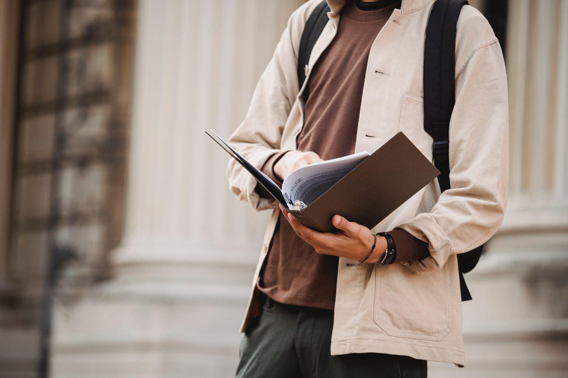student reading documents in folder outside university